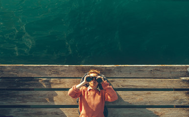 Young Beautiful Girl Lies On A Pier Near The Sea And Looks Through Binoculars On The Sky. Travel Search Journey Concept