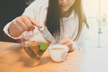 Woman pouring pouring tea in cup