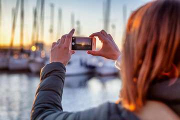 young woman take a photo of the sunset in the port on a mobile phone smartphone, travel photography, social networks