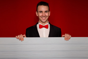 Young smiling man with blank red sign board. Handsome businessman holding banner with copyspace for advertising messages, posters and text. Photo for business projects, product presentation