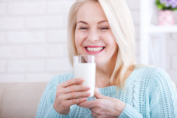 Happy middle aged woman drinking milk