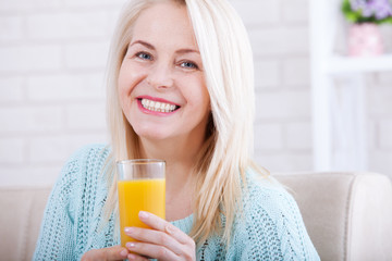 Woman drinking orange juice smiling. Beautiful middle aged Caucasian model face closeup.