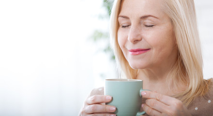 Portrait of happy blonde with mug in hands
