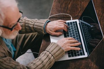Close-up view of elder man using laptop
