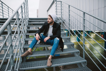 Bearded stylish man sitting on the stairs
