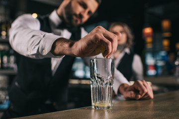Spoed Foto op Canvas male bartender squeezing out lemon juice into glass at bar