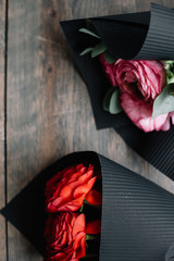 Two Ranunculus flower bouquets (with red and pink ranunculus) wrapped in black paper, lying on the wooden table background