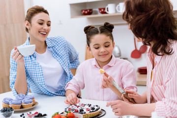 three generations of beautiful women spending time together on kitchen and eating desserts at kitchen
