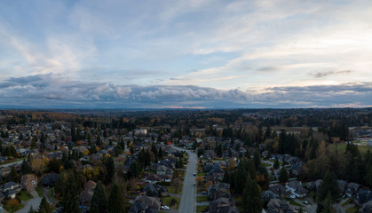 Aerial panoramic view of a suburban neighborhood during a vibrant and cloudy sunset. Taken in Greater Vancouver, British Columbia, Canada.