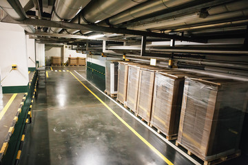 Industrial warehouse or logistic hangar interior. Boxes and pipelines in corridor