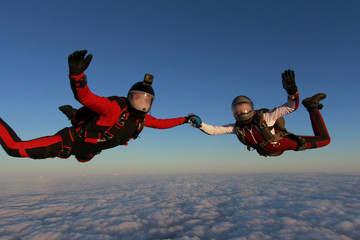 Two skydivers are in the winter sunset sky.