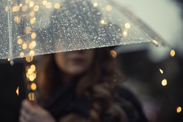 Blurred face of a woman behind transparent umbrella with rain drops Wall mural