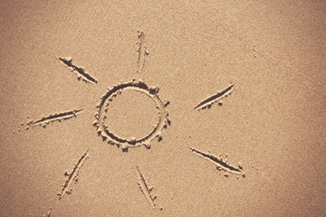 Sun drawing on beach sand.