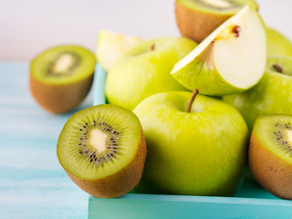 Green apples and kiwi on turquoise background