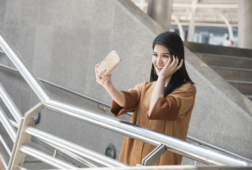 asian woman using smart phone taking a selfie photo in city.