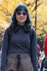 A trendy female traveller posing on the famous Genko Avenue with beautiful trees that have turned yellow in the autumn season in Meiji Jingu Gaien Park