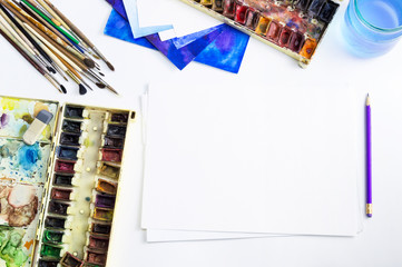 Top view of desk with paper and watercolor art