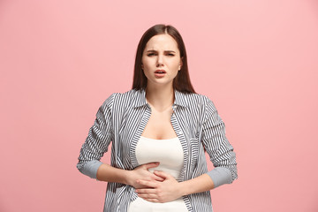 The stomach ache. The sad woman with stomach ache or pain on a pink studio background.