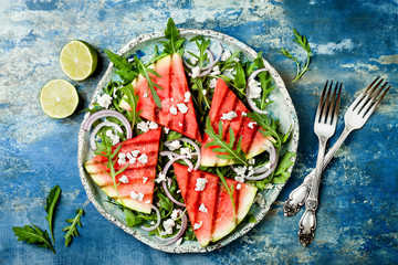 Fresh summer grilled watermelon salad with feta cheese, arugula, onions on blue background