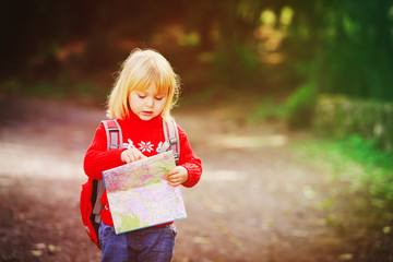 little girl travel hiking in nature looking at map