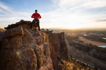Adventurous man is rappeling down a cliff during a bright and vibrant sunny sunset. Taken in Smith Rock, Oregon, North America.