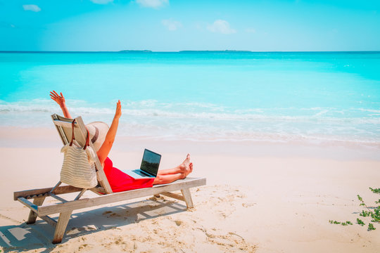 remote work concept -happy young woman with laptop on beach