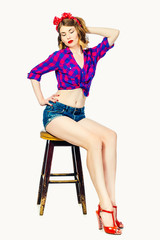 young woman in the style of pin-up on the chair
