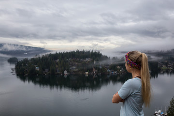 Young Caucasian Girl is enjoying a beautiful scenery from the top of a mountain during a cloudy winter morning. Taken in Quarry Rock, Deep Cove, North Vancouver, BC, Canada.