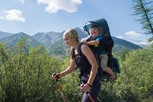 Woman Hiker trekking in mountains with child in backpack . Mother with baby boy travelling in summer sunny day.