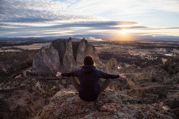 Adventurous man sitting in a meditation pose on top of a cliff during a vibrant sunset. Taken in Smith Rock, Oregon, America. Concept: adventure, freedom, travel, holiday, vacation