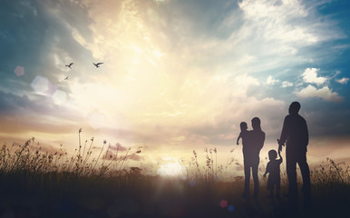 International migrants day concept: Father, mother and two son over meadow autumn sunset background