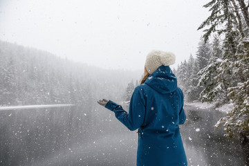 Woman enjoying the beautiful Canadian Winter Landscape during a snowy day. Taken near Squamish and Whistler, North of Vancouver, BC, Canada.