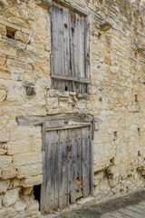 Two sets of very old wooden doors in a stone wall.