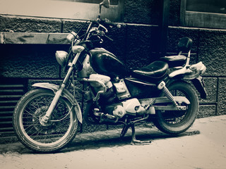 old black and white motorcycle parked in the roadside