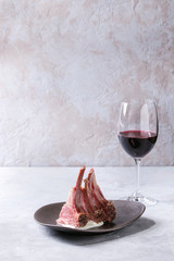 Grilled sliced rack of lamb with yogurt mint sauce served on ceramic plate with glass of red wine over grey texture table. Copy space