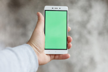 Closeup man hand holding and touching phone with green screen vertical
