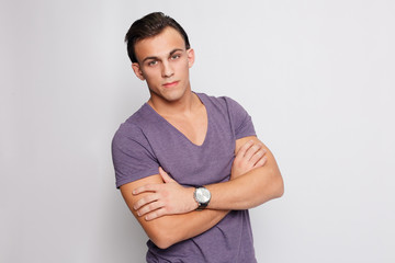 Handsome young man on grey background looking at camera