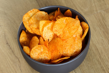 Spiced paprika Potato chips in a bowl on a wooden background