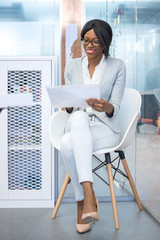 Young smiling African-american businesswoman or secretary sitting on the office chair and reading a document.