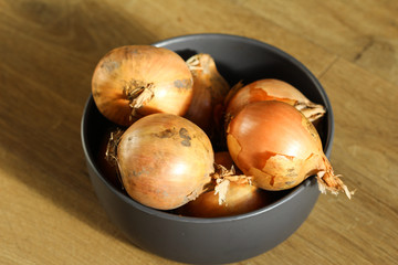 Bowl fresh ripe onions on wooden background