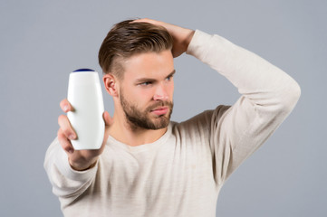 Man touch healthy hair with shampoo bottle in hand