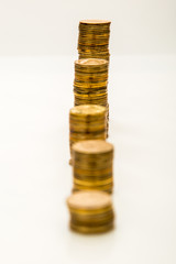 Stack of yellow coins in a row on a white background