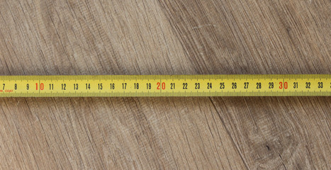 yellow measuring tape in centimeter (cm) on wooden background