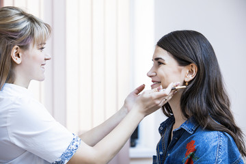 Beautician female carries out the correction of eyebrows on beautiful models in cosmetic cabinete