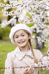 Pretty little girl in white blossom garden in beautiful spring day