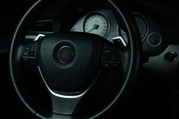 Cruscotto automobile mostra lo sterzo ed il contagiri auto in una fotografia a sfondo nero