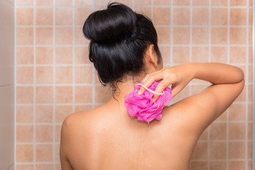 Portrait of beautiful woman taking shower with bath sponge and soap