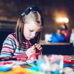 tailor art workshops for children - a girl sewing felt decorations