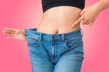 Young woman showing successful weight loss with her jeans on isolate background, Healthcare, Diet concept