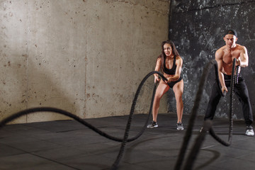 couple exercising with battle ropes at gym. Woman and man training together doing battling rope workout